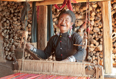 Weaver of the Ann tribe near Kyaing Tong. Her black teeth come from decades of chewing betel nuts @ Birgit Neiser