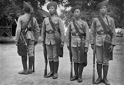 Three soldiers of the Kachin ethnic group and a soldier (back turned) from the Lishaw tribe. Bhamo. Northern Shan States @ Christine Scherman